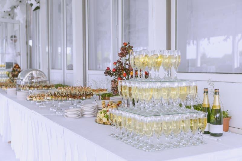 Τομέας εστιάσεως στο γεγονός, που χύνεται στα ποτήρια της σαμπάνιας, ένας υπέροχα διακοσμημένος πίνακας με τα πρόχειρα φαγητά στοκ φωτογραφίες