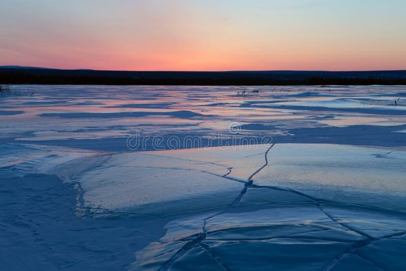 Τομέας πάγου στις ρωγμές και τον κόκκινο ουρανό στοκ εικόνες