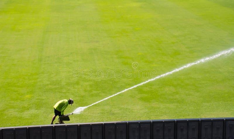 Τομέας χλόης ποδοσφαίρου ποτίσματος ατόμων rawn στοκ εικόνα