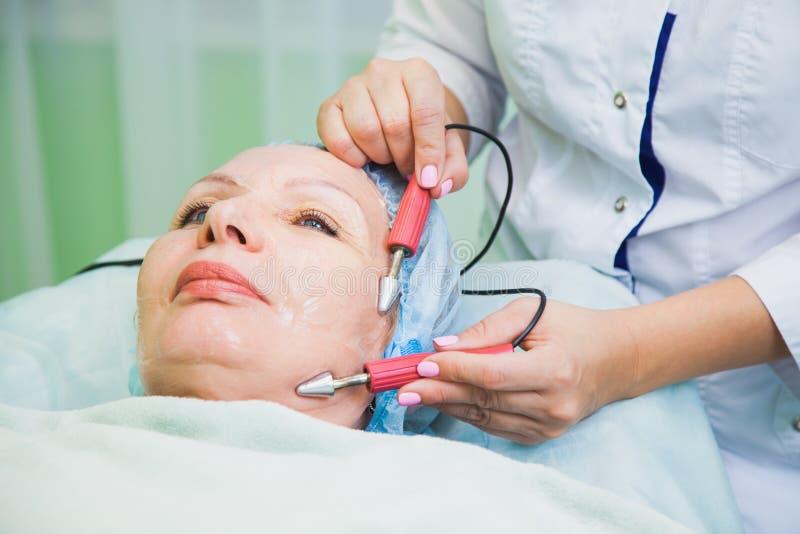 Τονίζοντας διαδικασία μυών για την ανώτερη γυναίκα cosmetology στην κλινική στοκ φωτογραφία