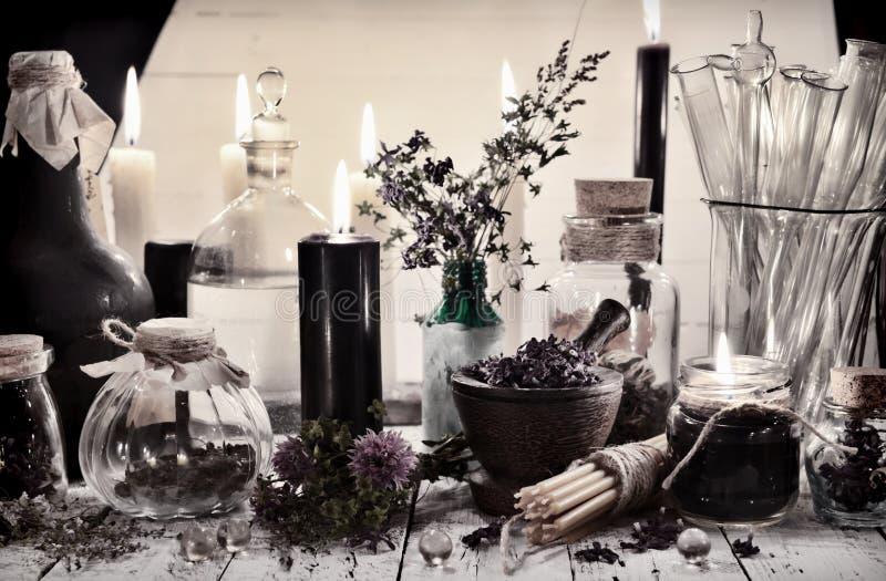 Τονισμένη ακόμα ζωή με το αλχημικά βάζο και τα μπουκάλια και απόκρυφα αντικείμενα στον πίνακα στοκ φωτογραφία