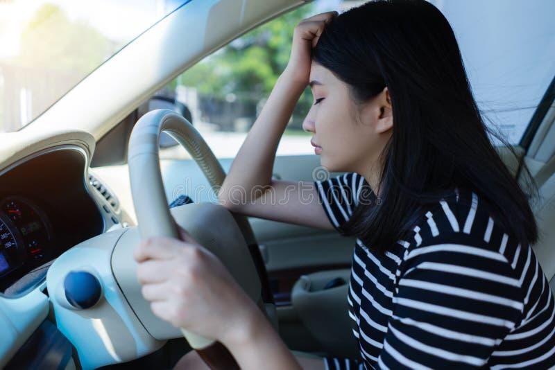Τονισμένη ασιατική συνεδρίαση οδηγών γυναικών στο αυτοκίνητο που έχει τη στάση πονοκέφαλου μετά από να οδηγήσει το αυτοκίνητο στη στοκ εικόνες