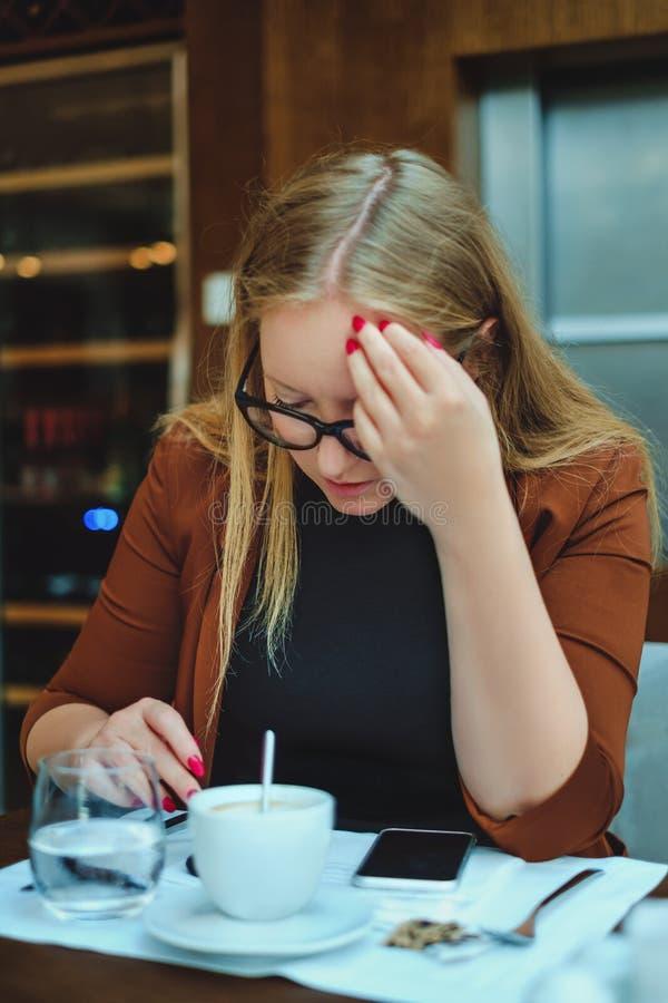 Τονισμένη γυναίκα που προσπαθεί να διαβάσει στο εστιατόριο στοκ φωτογραφία με δικαίωμα ελεύθερης χρήσης