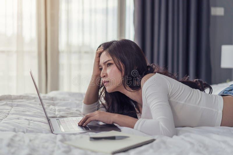 Τονισμένη γυναίκα που χρησιμοποιεί το φορητό προσωπικό υπολογιστή στο κρεβάτι στοκ εικόνα