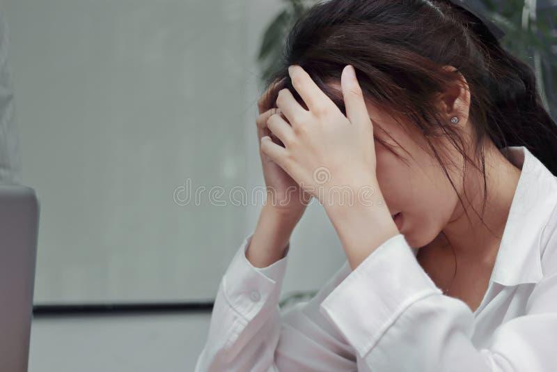 Τονισμένη εξαντλημένη νέα ασιατική επιχειρησιακή γυναίκα που πάσχει από τη βαριά κατάθλιψη στην αρχή στοκ εικόνες