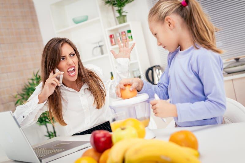 Τονισμένη επιχειρηματίας και η κόρη της το πρωί στο σπίτι στοκ εικόνες