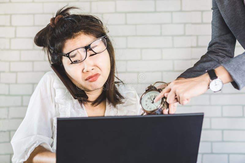 Τονισμένη θηλυκή ασιατική συνεδρίαση εργαζομένων στο γραφείο που αισθάνεται την πίεση από την ενόχληση του προϊσταμένου στοκ φωτογραφία