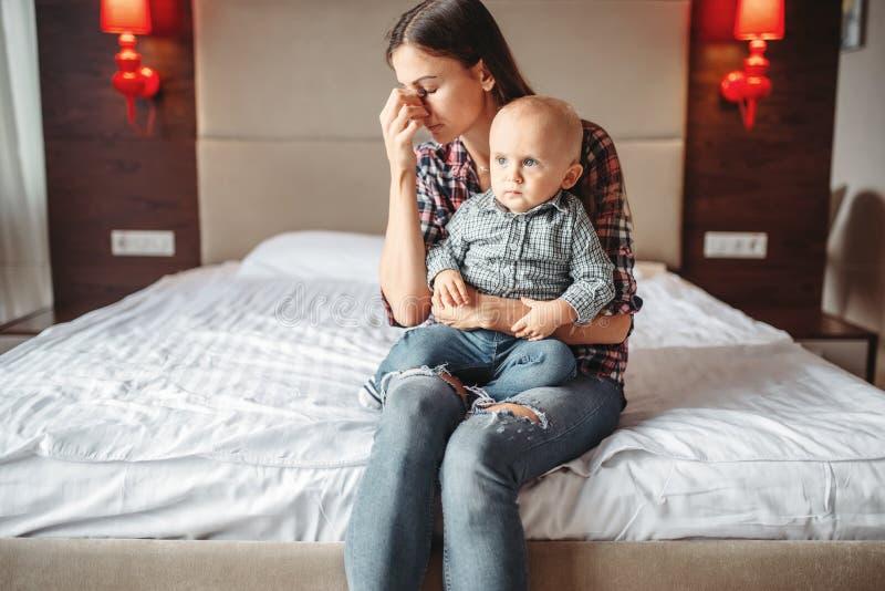 Τονισμένη μητέρα με λίγη συνεδρίαση παιδιών στο κρεβάτι στοκ εικόνα