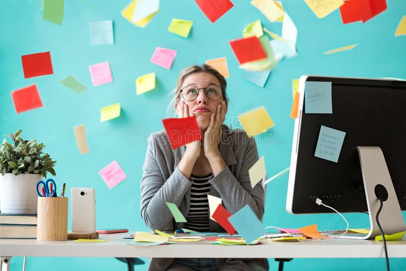 Τονισμένη νέα επιχειρησιακή γυναίκα που φαίνεται επάνω από post-its στο γραφείο στοκ εικόνες