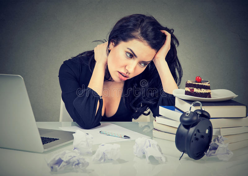 Τονισμένη συνεδρίαση γυναικών στο γραφείο γλυκό κέικ πόθου γραφείων της στο καταπονημένο στοκ εικόνα με δικαίωμα ελεύθερης χρήσης