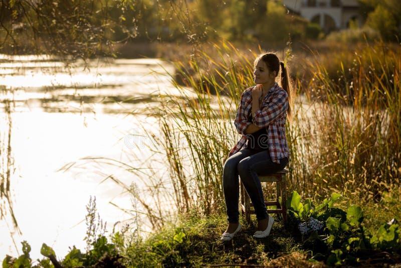 Τονισμένη φωτογραφία της συνεδρίασης γυναικών στο ηλιοβασίλεμα από τη λίμνη στοκ εικόνες