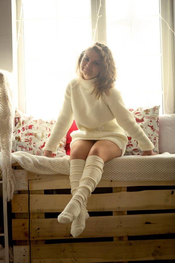 Τονισμένη φωτογραφία της χαριτωμένης γυναίκας στο πουλόβερ και των καλτσών που κάθονται στο παράθυρο στοκ εικόνες