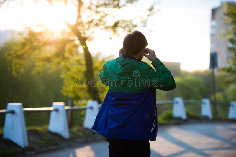 Τονισμένη φωτογραφία του κοινού νέου μόνου ατόμου που περπατά στην πόλη που ακούει στη μουσική με τα ακουστικά -αυτιών στο ηλιοβα στοκ εικόνες