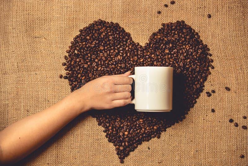 Τονισμένη φωτογραφία του προσώπου που κρατά την άσπρη κούπα ενάντια στην καρδιά του καφέ στοκ φωτογραφία