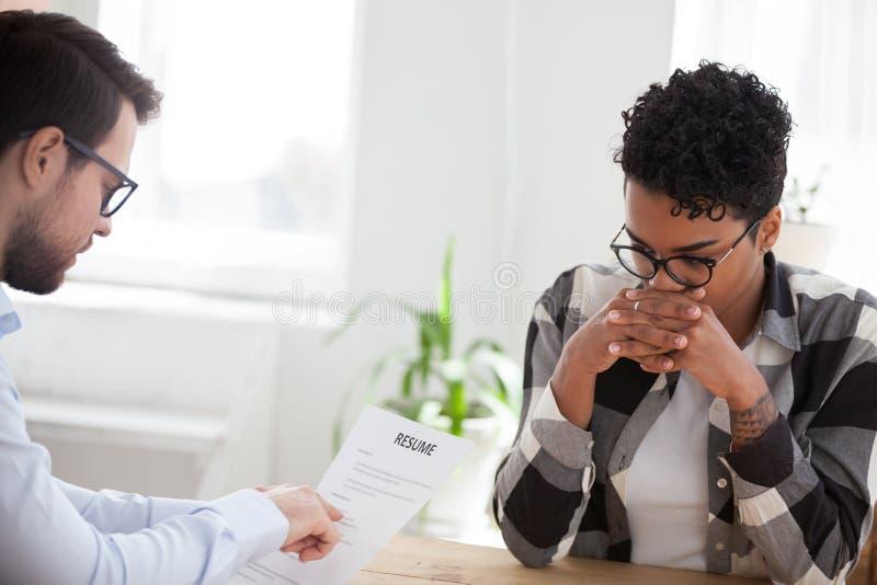 Τονισμένοι μαύρη γυναίκα και προϊστάμενος κατά τη διάρκεια της συνέντευξης εργασίας στοκ φωτογραφίες