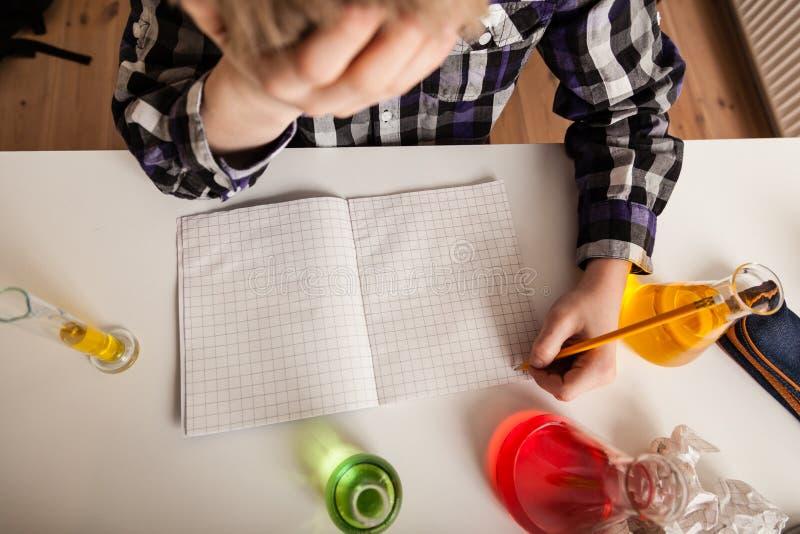 Τονισμένος έφηβος που κάνει την εργασία χημείας στοκ εικόνες με δικαίωμα ελεύθερης χρήσης