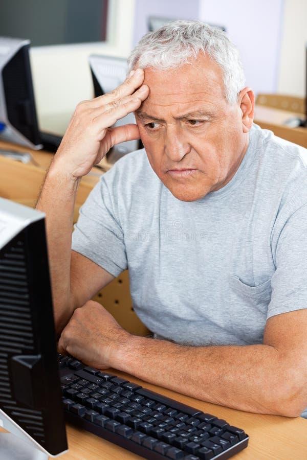 Τονισμένος ανώτερος σπουδαστής που εξετάζει τον υπολογιστή στοκ εικόνα με δικαίωμα ελεύθερης χρήσης