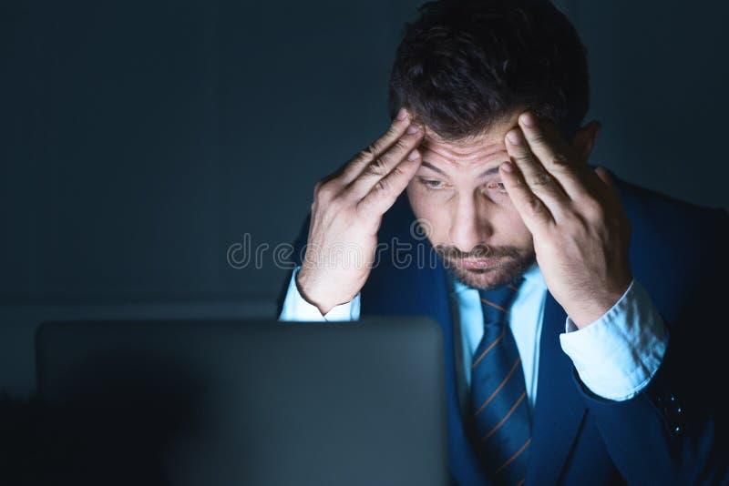 Τονισμένος επιχειρηματίας που χρησιμοποιεί το lap-top που λειτουργεί τη νύχτα στοκ εικόνα με δικαίωμα ελεύθερης χρήσης