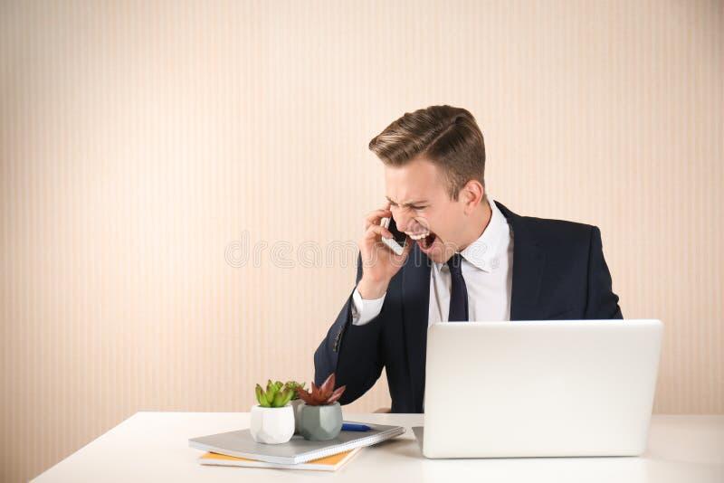 Τονισμένος νέος επιχειρηματίας που μιλά στο κινητό τηλέφωνο στον πίνακα στοκ φωτογραφία με δικαίωμα ελεύθερης χρήσης