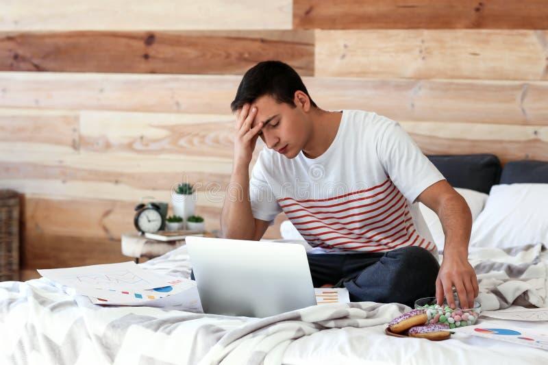 Τονισμένος νεαρός άνδρας που τρώει τα γλυκά εργαζόμενος στο lap-top στην κρεβατοκάμαρα στοκ εικόνα