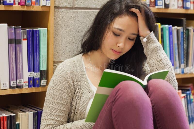 Τονισμένος σπουδαστής που διαβάζει ένα βιβλίο στοκ εικόνες