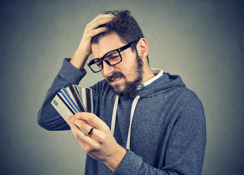 Τονισμένο άτομο που εξετάζει πάρα πολλές πιστωτικές κάρτες στοκ εικόνα