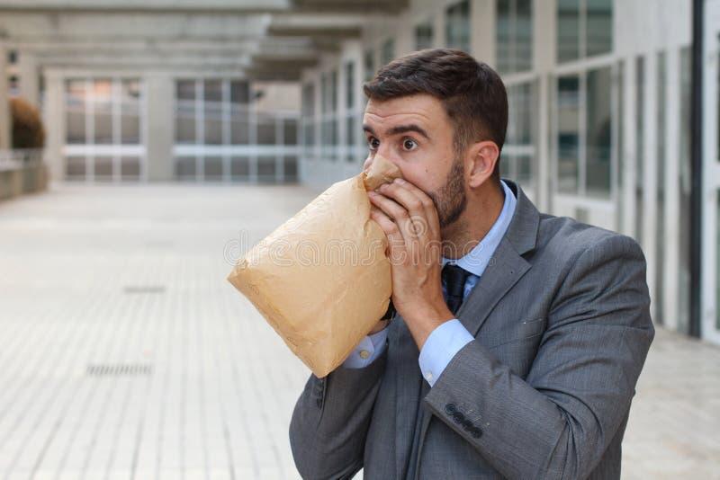 Τονισμένο έξω άτομο που αναπνέει μέσω της τσάντας εγγράφου στοκ φωτογραφία με δικαίωμα ελεύθερης χρήσης