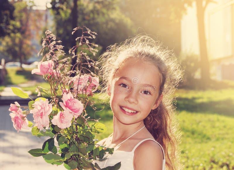 Τονισμένο πορτρέτο των ευτυχών beautyful τριαντάφυλλων και του χαμόγελου λαβής μικρών κοριτσιών στη θερινή ημέρα στοκ εικόνες με δικαίωμα ελεύθερης χρήσης