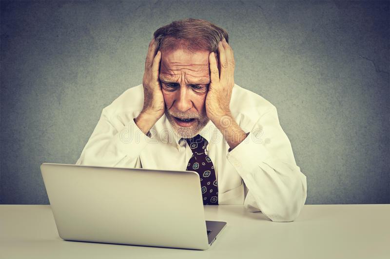 Τονισμένο πρεσβύτερος άτομο που εργάζεται στη συνεδρίαση lap-top στον πίνακα στοκ εικόνα