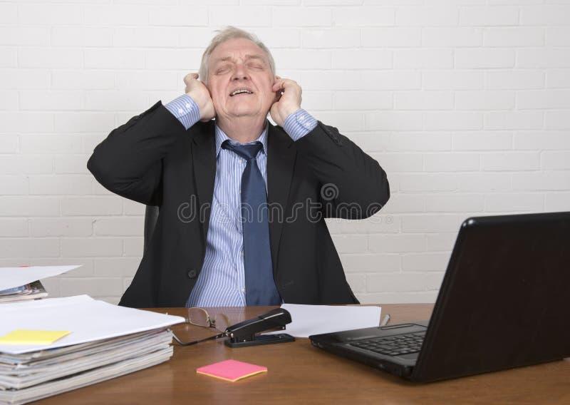 Τονισμένο ώριμο άτομο στην εργασία που καλύπτει τα αυτιά του στοκ εικόνα με δικαίωμα ελεύθερης χρήσης