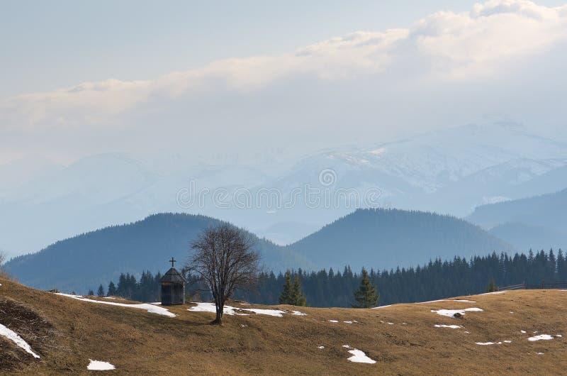 Τοπίο άνοιξη με ένα παρεκκλησι στα βουνά στοκ φωτογραφίες