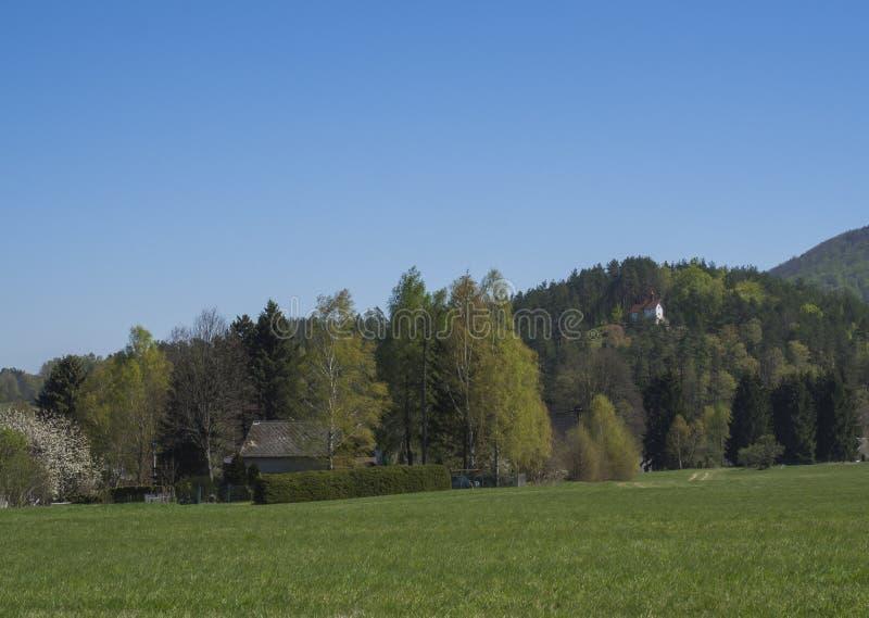 Τοπίο άνοιξη με την άποψη σχετικά με το χωριό Marenice στα βουνά Lusitian με το μικρό παρεκκλησι στο λόφο, πολύβλαστο πράσινο λιβ στοκ εικόνες με δικαίωμα ελεύθερης χρήσης