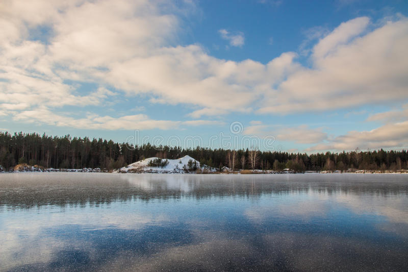 τοπίο αγροτικό Όμορφος χειμερινός ουρανός πέρα από τη χιονώδη και παγωμένη λίμνη στοκ εικόνα