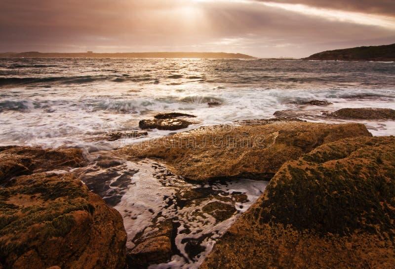 Τοπίο ανατολής του ωκεανού με τα σύννεφα και τους βράχους κυμάτων στοκ εικόνα με δικαίωμα ελεύθερης χρήσης