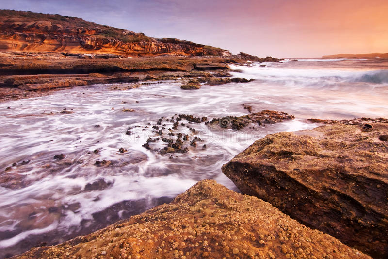 Τοπίο ανατολής του ωκεανού με τα σύννεφα και τους βράχους κυμάτων στοκ φωτογραφίες