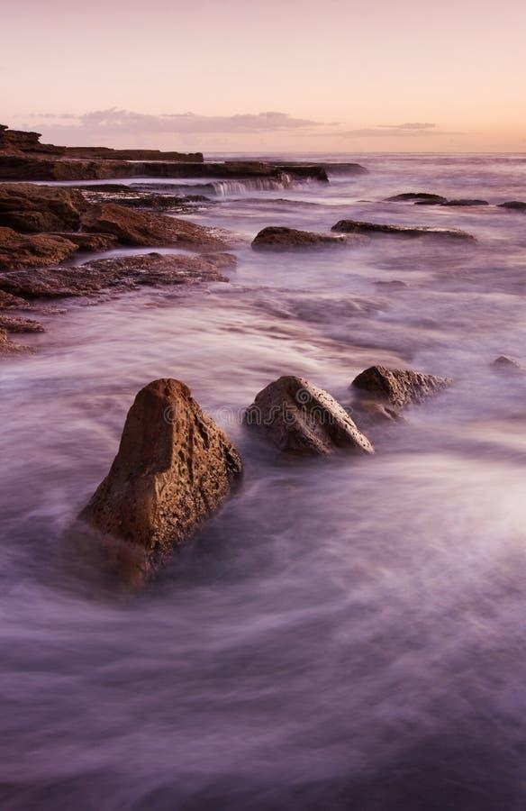 Τοπίο ανατολής του ωκεανού με τα σύννεφα και τους βράχους κυμάτων στοκ φωτογραφίες με δικαίωμα ελεύθερης χρήσης