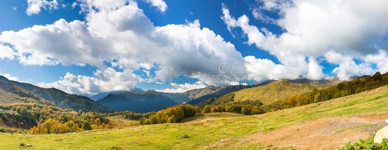 Τοπίο βουνών πανοράματος με το μπλε ουρανό και τα άσπρα σύννεφα στοκ εικόνα