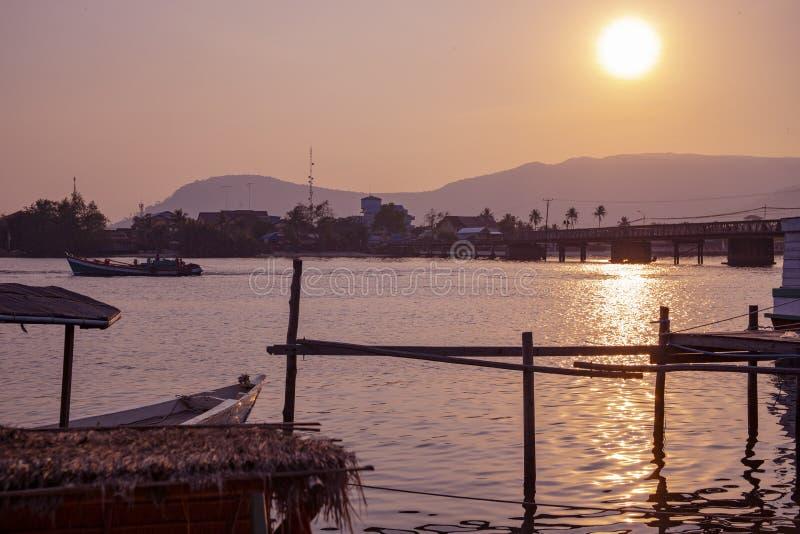 Τοπίο ηλιοβασιλέματος με ακόμα τον ποταμό και τον αγροτικό κόλπο Ρομαντικό ηλιοβασίλεμα στην τροπική χώρα Αστικοί γέφυρα και κόλπ στοκ εικόνα