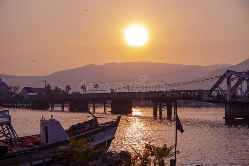Τοπίο ηλιοβασιλέματος με ακόμα τον ποταμό και τα απόμακρα βουνά Ρομαντικό ηλιοβασίλεμα στην τροπική χώρα Αστικοί γέφυρα και κόλπο στοκ φωτογραφία με δικαίωμα ελεύθερης χρήσης