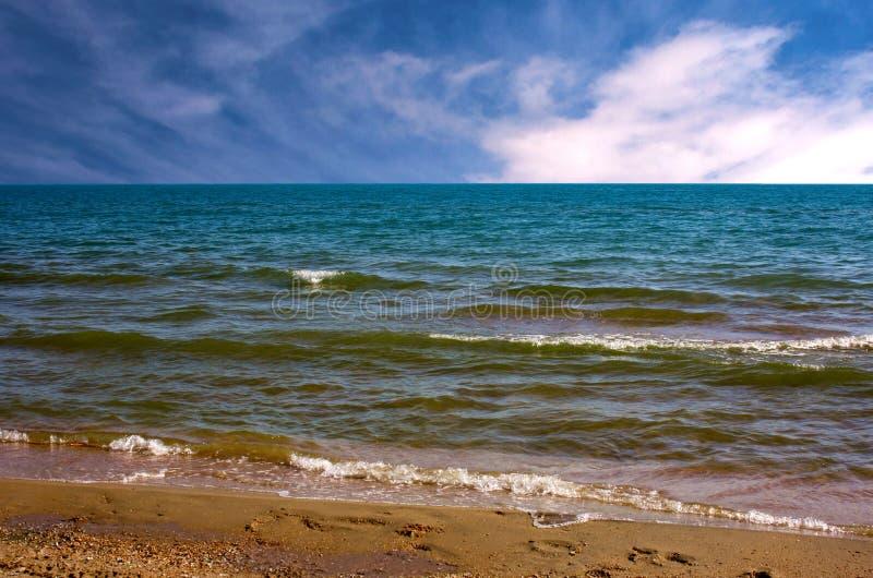Τοπίο θάλασσας με έναν μικρό ενθουσιασμό στη θάλασσα, τα φωτεινά κύματα και τα πουπουλένια σύννεφα στον ουρανό στοκ εικόνες