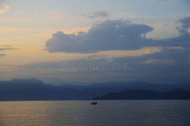 Τοπίο λιμνών και βουνών με την πλέοντας βάρκα στην μπλε ώρα στοκ φωτογραφία