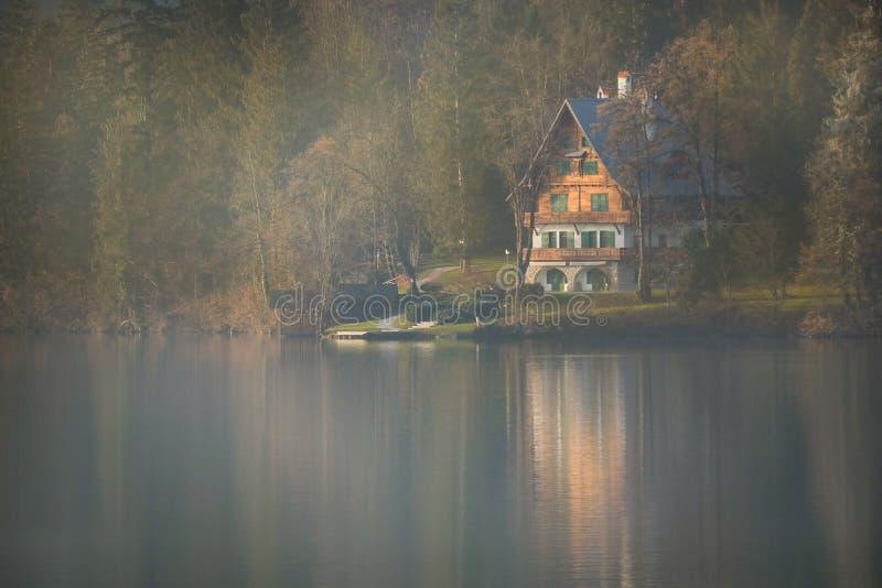 Τοπίο με την καμπίνα στη λίμνη που αιμορραγείται στοκ εικόνες