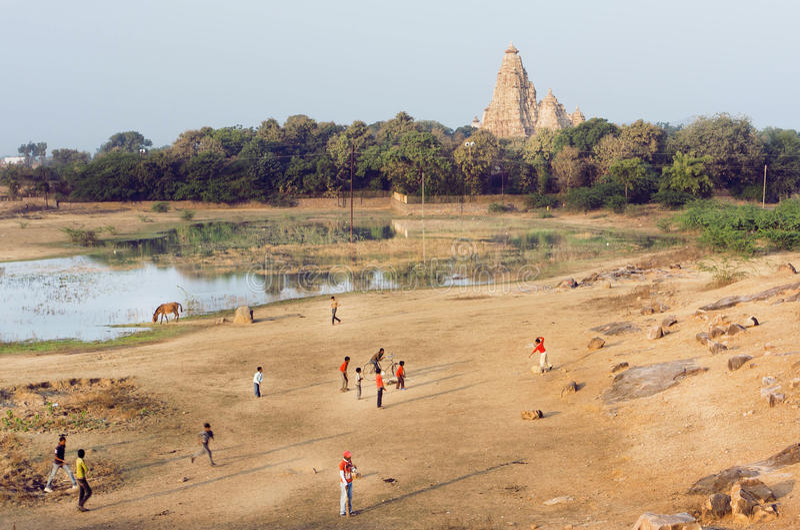 Τοπίο με τον ινδό ναό Khajuraho και των παιδιών που παίζουν το γρύλο, Ινδία στοκ φωτογραφία