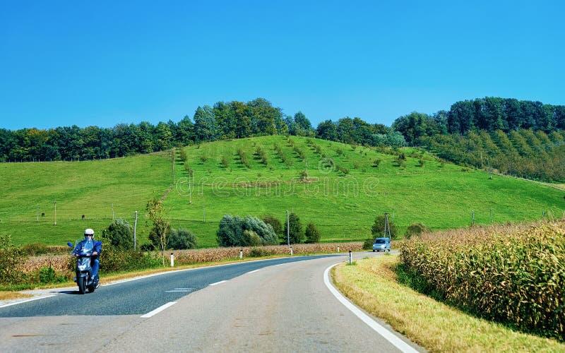 Τοπίο με τους λόφους και τη μοτοσικλέτα στο δρόμο Maribor Σλοβενία στοκ εικόνα