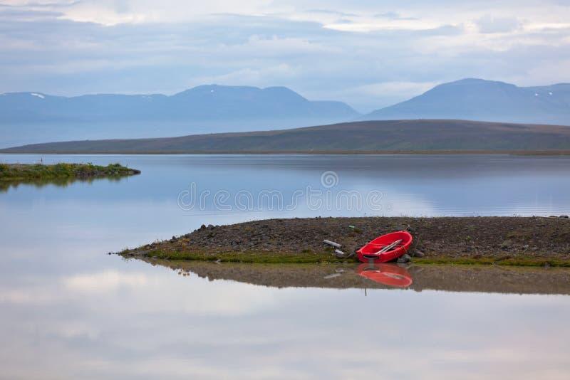 Τοπίο νερού της Ισλανδίας με την κόκκινη βάρκα στοκ εικόνα
