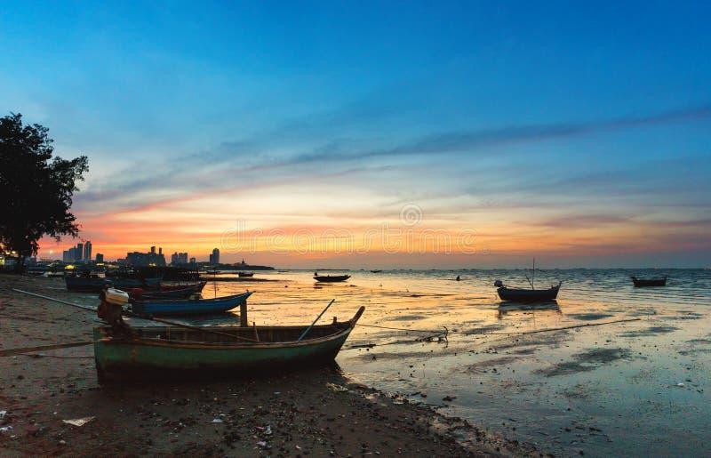 Τοπίο της τροπικής παραλίας με το παλαιό αλιευτικό σκάφος που σταθμεύουν στην παραλία στο ηλιοβασίλεμα λυκόφατος σε Pattaya, Ταϊλ στοκ εικόνα