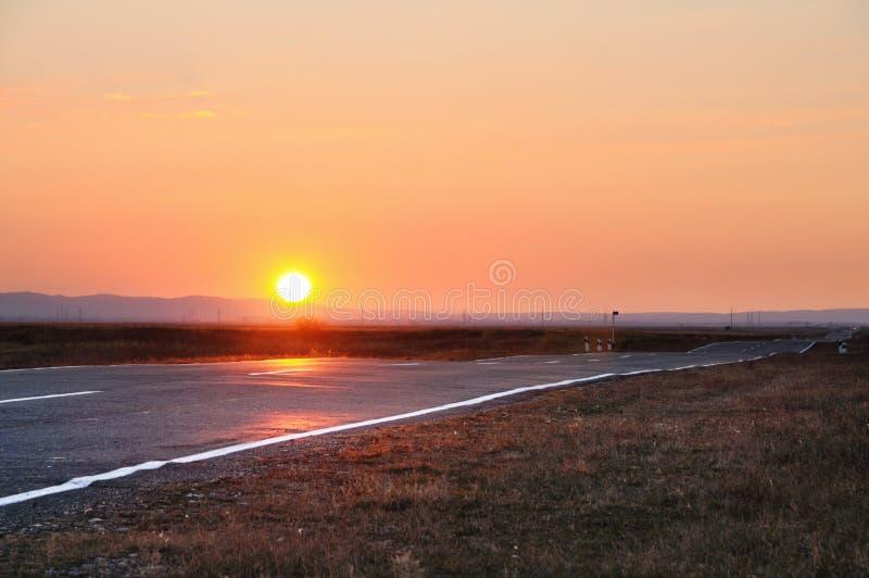 Τοπίο φθινοπώρου με έναν δρόμο ασφάλτου και θεαματικό ηλιοβασίλεμα επάνω από τα βουνά στον ορίζοντα στοκ εικόνα με δικαίωμα ελεύθερης χρήσης