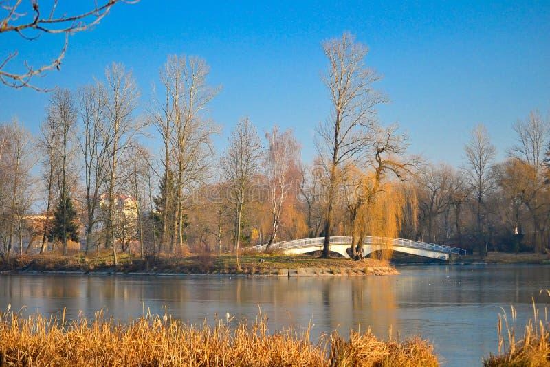 Τοπίο φθινοπώρου μιας λίμνης πόλεων με μια γέφυρα στο νησί σε το στοκ φωτογραφίες