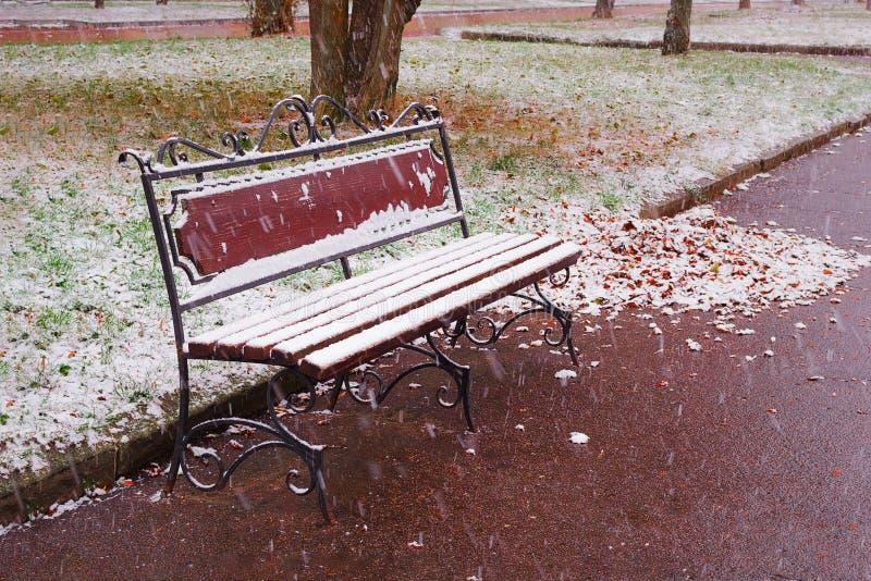 Τοπίο φθινοπώρου: Παλαιός πάγκος κήπων στα τέλη του φθινοπώρου που καλύπτεται από το πρώτο χιόνι στοκ εικόνες