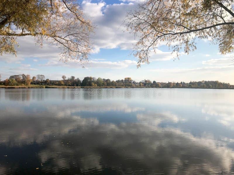 Τοπίο φθινοπώρου όμορφο με τα δέντρα και τα κίτρινα φύλλα στη λίμνη ενάντια στο μπλε ουρανό μια ηλιόλουστη ημέρα στοκ εικόνα